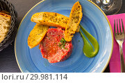 Купить «Picture of raw veal steak tartar served at blue plate with fried toasts», фото № 29981114, снято 16 июня 2019 г. (c) Яков Филимонов / Фотобанк Лори