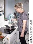 Купить «Young woman making pancakes on the kitchen», фото № 29981290, снято 11 декабря 2018 г. (c) Константин Шишкин / Фотобанк Лори