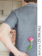 Man hiding flower behind his back for wife. Стоковое фото, агентство Wavebreak Media / Фотобанк Лори