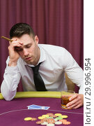 Купить «Man leaning on poker table holding cigar», фото № 29996954, снято 20 июля 2012 г. (c) Wavebreak Media / Фотобанк Лори