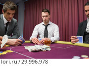 Купить «Men looking at their hands in high stakes poker game», фото № 29996978, снято 20 июля 2012 г. (c) Wavebreak Media / Фотобанк Лори