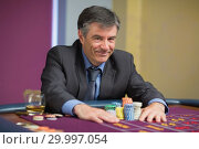 Купить «Man smiling and taking his chips», фото № 29997054, снято 20 июля 2012 г. (c) Wavebreak Media / Фотобанк Лори