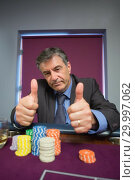 Купить «Man giving thumbs up at roulette table», фото № 29997062, снято 20 июля 2012 г. (c) Wavebreak Media / Фотобанк Лори