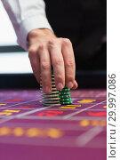Купить «Dealer placing chips on table», фото № 29997086, снято 20 июля 2012 г. (c) Wavebreak Media / Фотобанк Лори