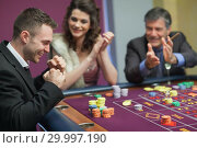 Купить «People cheering man at craps game», фото № 29997190, снято 20 июля 2012 г. (c) Wavebreak Media / Фотобанк Лори