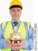 Купить «Man holding piggy bank with money», фото № 29998882, снято 31 июля 2012 г. (c) Wavebreak Media / Фотобанк Лори