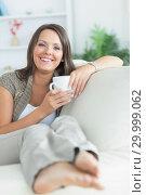 Купить «Happy woman drinking a mug on the sofa», фото № 29999062, снято 16 августа 2012 г. (c) Wavebreak Media / Фотобанк Лори