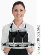 Купить «Waitress holding two glasses of wine», фото № 30002562, снято 28 августа 2012 г. (c) Wavebreak Media / Фотобанк Лори