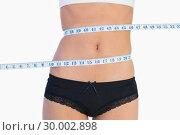 Купить «Slim belly surrounded by measuring tape», фото № 30002898, снято 19 апреля 2013 г. (c) Wavebreak Media / Фотобанк Лори