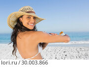 Купить «Smiling attractive brunette with straw hat putting on sun cream», фото № 30003866, снято 4 апреля 2013 г. (c) Wavebreak Media / Фотобанк Лори