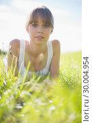 Купить «Pretty woman lying on the grass», фото № 30004954, снято 26 апреля 2013 г. (c) Wavebreak Media / Фотобанк Лори