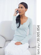 Shocked attractive woman sitting on cosy sofa having a phone call. Стоковое фото, агентство Wavebreak Media / Фотобанк Лори