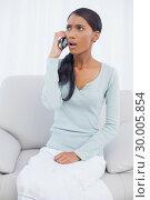 Купить «Shocked attractive woman sitting on cosy sofa having a phone call», фото № 30005854, снято 23 мая 2013 г. (c) Wavebreak Media / Фотобанк Лори