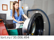 Купить «Woman in uniform taking out clothes from washing machine at laundry», фото № 30006494, снято 22 января 2019 г. (c) Яков Филимонов / Фотобанк Лори