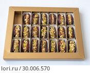 Купить «Dates stuffed with pistachios in a box», фото № 30006570, снято 13 апреля 2018 г. (c) Володина Ольга / Фотобанк Лори