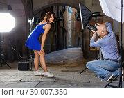 Купить «Professional photo shooting outdoors. Attractive female model posing to photographer on city street», фото № 30007350, снято 5 октября 2018 г. (c) Яков Филимонов / Фотобанк Лори