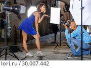 Купить «Professional photo shooting outdoors. Attractive female model posing to photographer on city street», фото № 30007442, снято 5 октября 2018 г. (c) Яков Филимонов / Фотобанк Лори