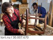 Купить «Woman artisan inspecting old chair», фото № 30007670, снято 2 февраля 2019 г. (c) Яков Филимонов / Фотобанк Лори