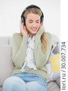 Купить «Happy cute blonde listening to music sitting on cosy sofa», фото № 30007734, снято 12 июня 2013 г. (c) Wavebreak Media / Фотобанк Лори