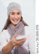 Купить «Smiling brunette with winter hat on holding remote», фото № 30009070, снято 22 мая 2013 г. (c) Wavebreak Media / Фотобанк Лори