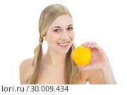 Купить «Smiling young blonde woman holding an orange», фото № 30009434, снято 6 июня 2013 г. (c) Wavebreak Media / Фотобанк Лори