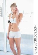 Купить «Concentrated young blonde model listening to music», фото № 30009534, снято 6 июня 2013 г. (c) Wavebreak Media / Фотобанк Лори