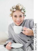 Купить «Pleased relaxed blonde woman in hair curlers enjoying a cup of coffee», фото № 30009634, снято 6 июня 2013 г. (c) Wavebreak Media / Фотобанк Лори