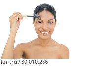 Купить «Smiling black haired model using eyebrow brush», фото № 30010286, снято 24 мая 2013 г. (c) Wavebreak Media / Фотобанк Лори