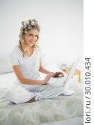Купить «Cheerful cute blonde wearing hair curlers using laptop», фото № 30010434, снято 11 июня 2013 г. (c) Wavebreak Media / Фотобанк Лори