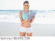 Купить «Smiling slender blonde in sportswear using tablet», фото № 30010734, снято 11 июня 2013 г. (c) Wavebreak Media / Фотобанк Лори