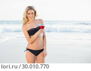 Купить «Gorgeous blonde in elegant bikini holding cocktail», фото № 30010770, снято 11 июня 2013 г. (c) Wavebreak Media / Фотобанк Лори