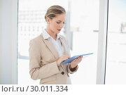 Купить «Focused blonde businesswoman using tablet pc», фото № 30011334, снято 31 мая 2013 г. (c) Wavebreak Media / Фотобанк Лори
