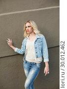 Купить «Serious casual blonde wearing denim clothes posing outdoors», фото № 30012462, снято 15 мая 2013 г. (c) Wavebreak Media / Фотобанк Лори