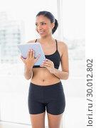 Dreamy dark haired model in sportswear holding a tablet pc. Стоковое фото, агентство Wavebreak Media / Фотобанк Лори