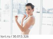 Dynamic fit brown haired model in sportswear showing her muscles. Стоковое фото, агентство Wavebreak Media / Фотобанк Лори