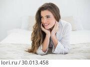 Купить «Pensive casual brown haired woman in white pajamas lying on her bed», фото № 30013458, снято 18 июня 2013 г. (c) Wavebreak Media / Фотобанк Лори