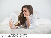 Купить «Cheerful casual brown haired woman in white pajamas holding a plush sheep», фото № 30013470, снято 18 июня 2013 г. (c) Wavebreak Media / Фотобанк Лори