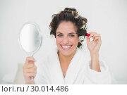 Купить «Cheerful natural brunette holding mascara», фото № 30014486, снято 21 июня 2013 г. (c) Wavebreak Media / Фотобанк Лори