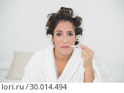 Купить «Sad natural brunette using thermometer», фото № 30014494, снято 21 июня 2013 г. (c) Wavebreak Media / Фотобанк Лори