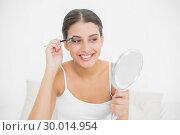 Купить «Pleased young brown haired model in white pajamas plucking her eyebrows», фото № 30014954, снято 25 июня 2013 г. (c) Wavebreak Media / Фотобанк Лори