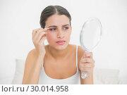 Купить «Frowning young brown haired model in white pajamas plucking her eyebrows», фото № 30014958, снято 25 июня 2013 г. (c) Wavebreak Media / Фотобанк Лори