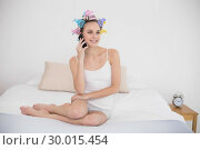 Dreamy natural brown haired woman in hair curlers making a phone call. Стоковое фото, агентство Wavebreak Media / Фотобанк Лори