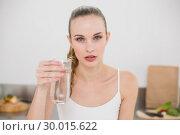Купить «Serious young woman holding glass of water», фото № 30015622, снято 26 июня 2013 г. (c) Wavebreak Media / Фотобанк Лори