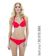 Купить «Pretty serious blonde model looking at camera wearing bikini», фото № 30015886, снято 28 июня 2013 г. (c) Wavebreak Media / Фотобанк Лори