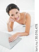 Купить «Smiling casual brunette in white pajamas using a laptop», фото № 30016478, снято 5 июля 2013 г. (c) Wavebreak Media / Фотобанк Лори