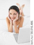 Купить «Happy casual brunette in white pajamas lying on her bed and looking at camera», фото № 30016486, снято 5 июля 2013 г. (c) Wavebreak Media / Фотобанк Лори