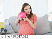 Купить «Beautiful pregnant woman shaking a piggy bank sitting on couch», фото № 30017022, снято 27 июня 2013 г. (c) Wavebreak Media / Фотобанк Лори