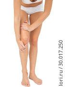 Купить «Young woman touching her injured knee», фото № 30017250, снято 31 июля 2013 г. (c) Wavebreak Media / Фотобанк Лори