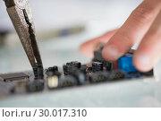 Купить «Extreme close up of pliers repairing hardware held by hand», фото № 30017310, снято 28 июня 2013 г. (c) Wavebreak Media / Фотобанк Лори