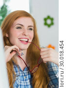 Купить «Beautiful redhead sitting at her desk and biting her glasses», фото № 30018454, снято 15 августа 2013 г. (c) Wavebreak Media / Фотобанк Лори
